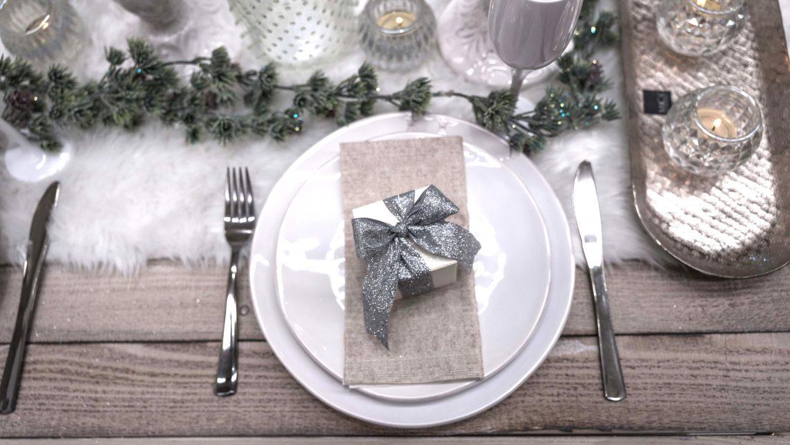 Tavola natalizia, con pacchettino regalo e nastro in argento glitter come segnaposto.